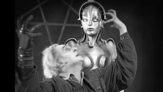 Ein metallischer Roboter mit Frauengesicht steht hinter einem Mann, der exstatisch die Hände verwirft.