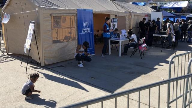 Kinder spielen vor einem Zelt des UNHCR.