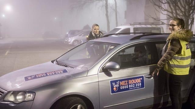 Fahrerinnen stehen im Nebel bei einem Auto mit Nez Rouge-Aufkleber