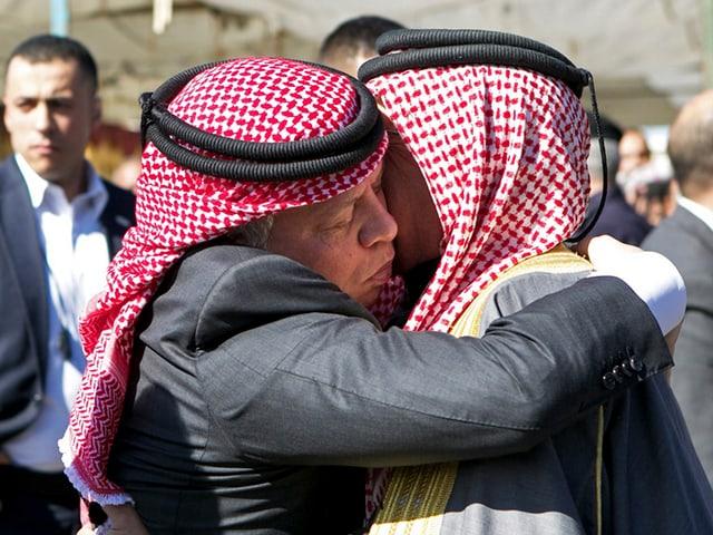 König Abdullah umarmt den Vater des Opfers. Beide haben eine traditionelle Kufya.