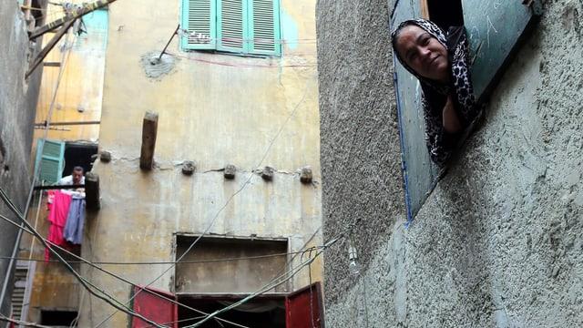 Menschen schauen aus Fenstern in einer Gasse des Bulaq-Viertels in Kairo