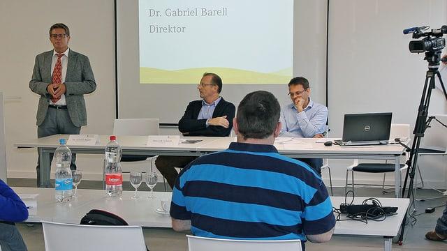 Ein Mann referiert vor einer Powerpoint-Präsentation. Fünf Personen hören ihm zu.