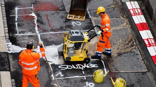Bauarbeiter schneiden den Belag einer Strasse auf.