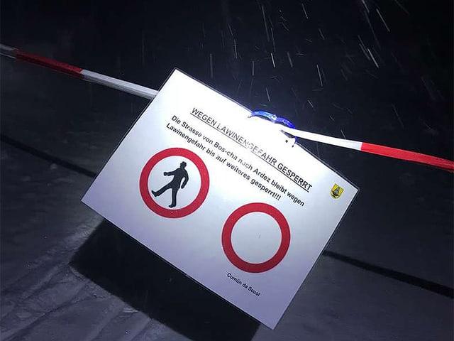 Gesperrte Strasse mit Absperrband und Warnschild.