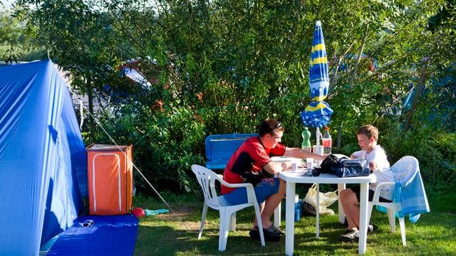 Ein Mann und ein Kind auf weissen Stühlen und an einem weissen Tisch beim Essen auf dem Campingplatz. Daneben ein blaues Zelt.