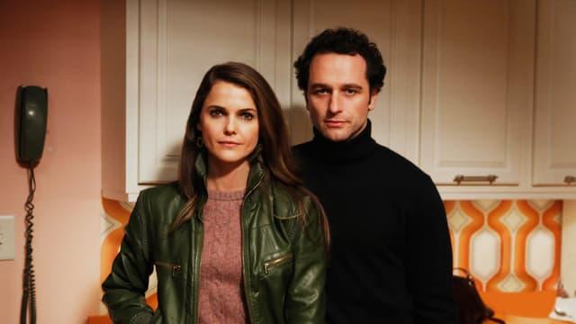 Eine Frau und ein Mann stehen in der Küche.