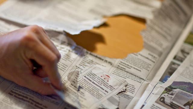 Hand reisst Stelleninserat aus Zeitung.
