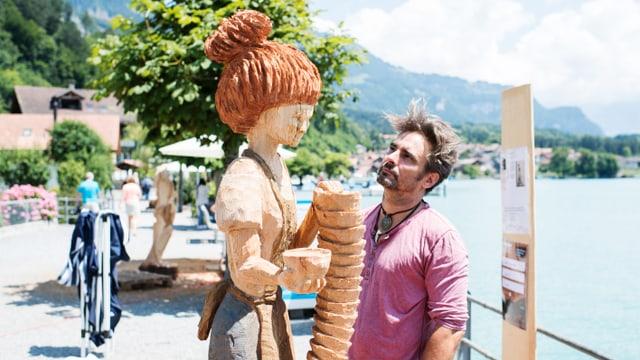 Ein Mann bestaunt seine Holzskulptur