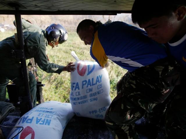 Männer werfen Reissäcke aus einem fliegenden Helikopter.
