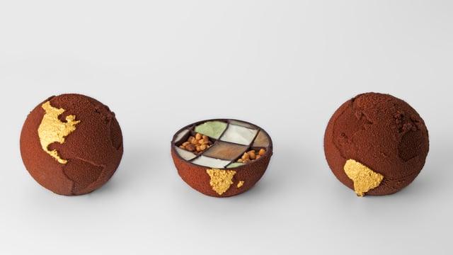 Eine Schokoladen-Weltkugel, auf die eine Kontinent mit Gold graviert ist.