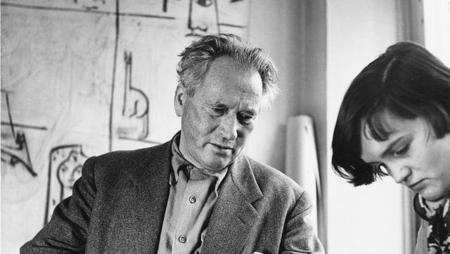 Ein Schwarz-Weiss-Bild des Kunstmalers in einem Atelier der Schule, daneben eine junge Studentin.