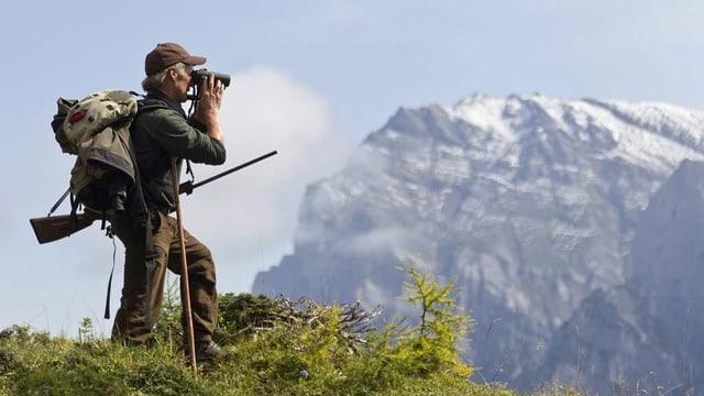 Ein Jäger steht auf einem Vorsprung und sucht mit dem Feldstecher nach Wild.