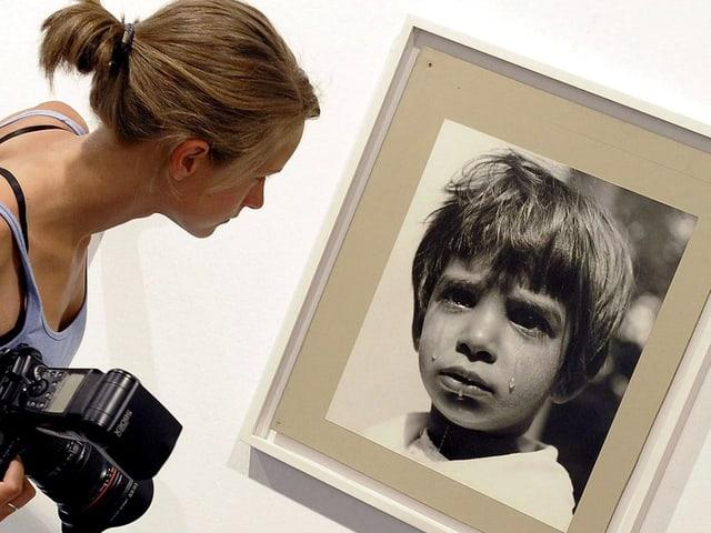 Eine Frau schaut auf das Foto eines weinenden Jungen.