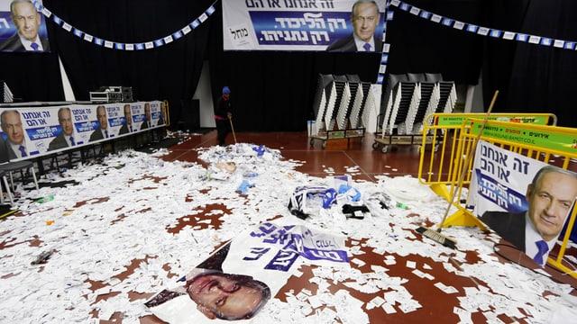 Wahlplakate auf dem Boden in einem leeren Saal.