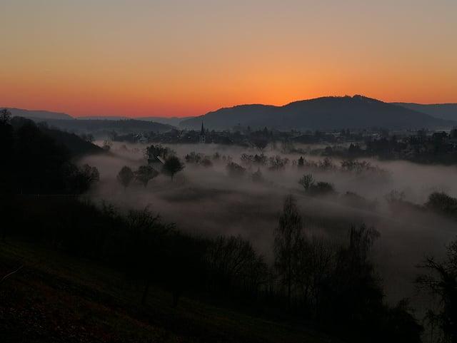 Im Tal liegt ein Nebelschlauch, der zur Seite etwas ausfranst. Auf der gegenüberliegenden Uferseite ist ein Kirchturm und ein Dorf zu sehen. Der wolkenlose Himmel leuchtet herrlich in warmen rot und orange Tönen.