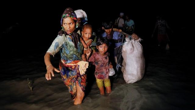 Eine Frau mit Kindern sowie ein schwer beladener Mann waten bei Nacht durchs knietiefe Wassesr.