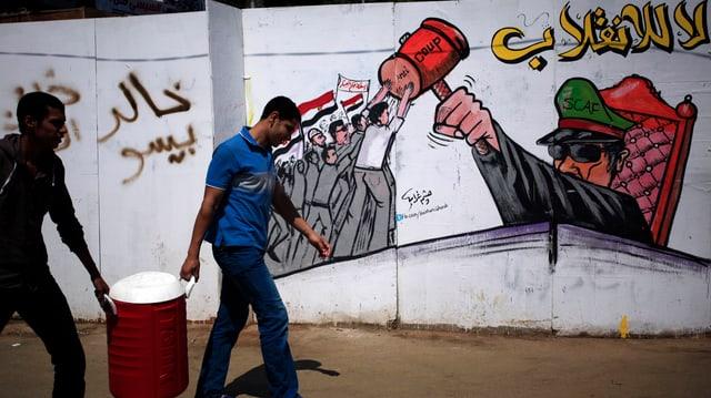 Zwei junge Männer gehen an einer Wand vorbei, darauf ein Grafitti: Mursi-Anhänger wehren sich gegen den Militärchef.