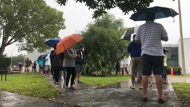 Menschen stehen Schlange mit Regenschirmen