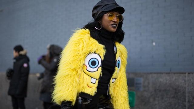Eine Frau mit einer Felljacke mit dem Gesicht von Spongebob.
