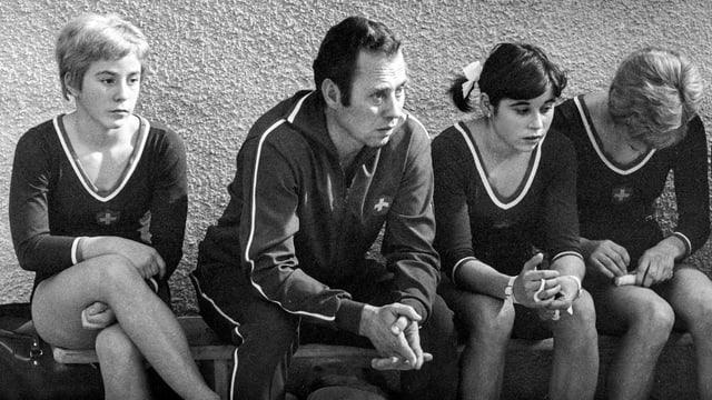 Ludek Martschini sitzt auf einer Aufnahme aus dem Jahr 1969 mit seinen Kunsturnerinnen auf einer Bank.