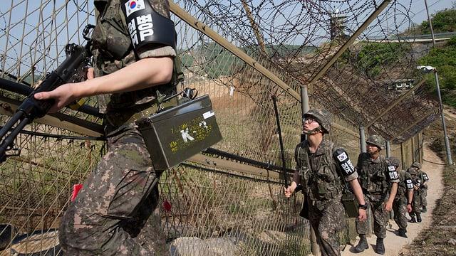 Soldaten laufen einen Stacheldrahtzaun entlang.