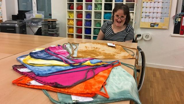 Eine Frau im Rollstuhl zeigt batik-gefärbte Baumwolltaschen in der Werkstatt des Wagerenhofs.