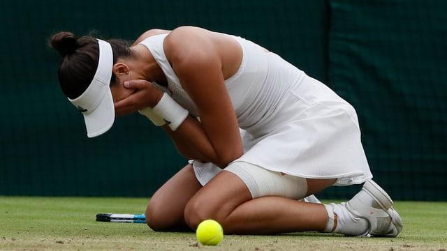 Giugadra da tennis cun mauns davant la fatscha.