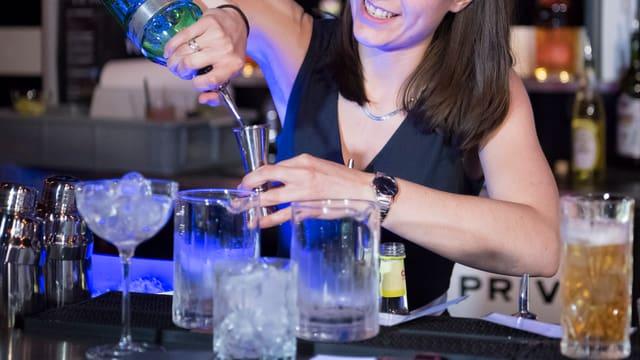 Barkeeperin schenkt einen Drink ein