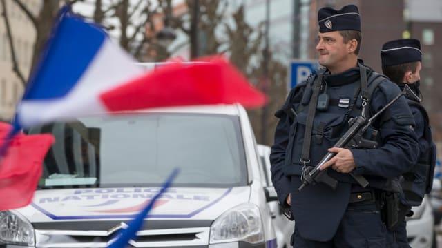 Ein Polizeibeamter des CRS-Korps (Compagnies Républicaines de Sécurité) patroulliert mit einer Waffe.
