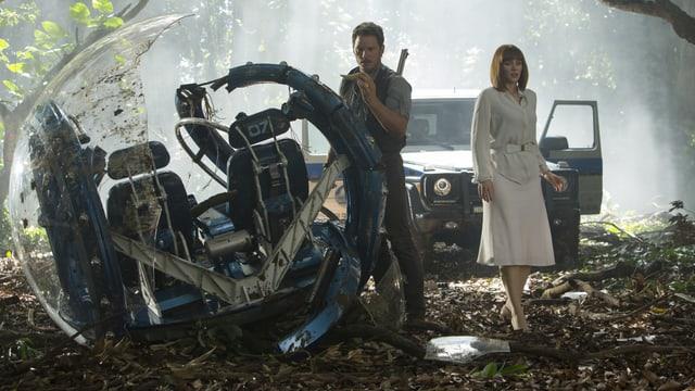 Mann und Frau mit geilem Auto im Wald. Sie wirken verloren. Ein seltsames Vehikel ist kaputt.