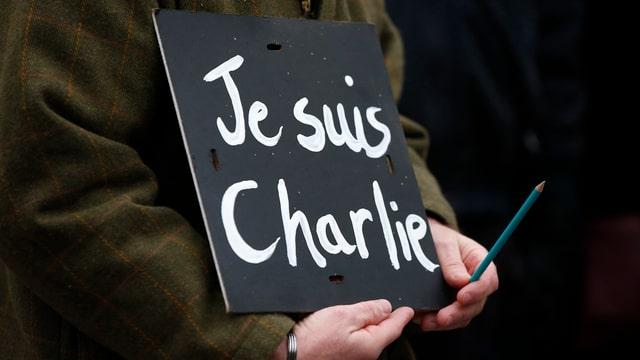 """Eine Person hält ein Schild mit der Aufschrift """"Je suis Charlie"""" und einen Bleistift in den Händen."""