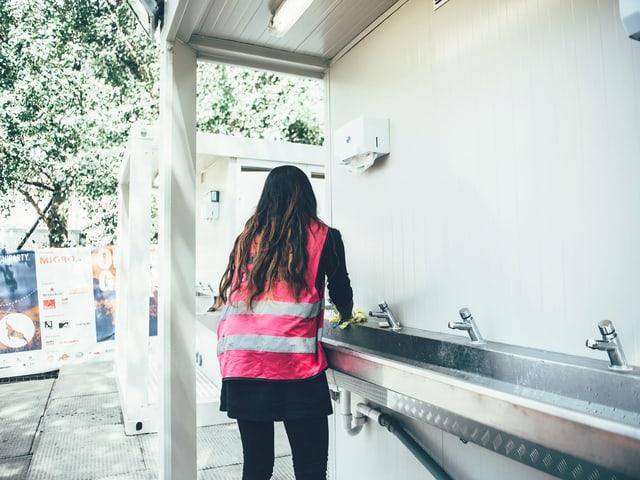Asylsuchende schrubbt ein Lavabo am Openair Gampel.