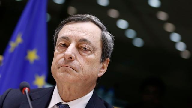 Mario Draghi schaut in die Kamera, vor ihm ein Mikrofon, hinter ihm eine EU-Flagge.