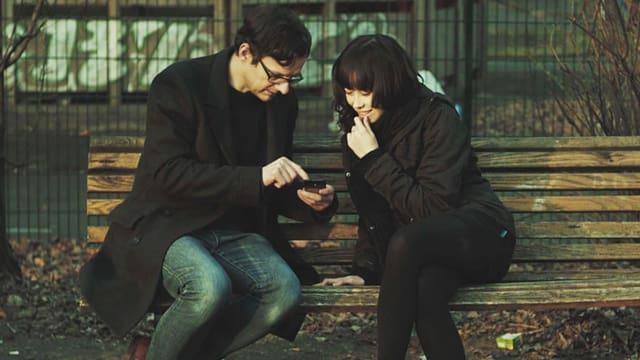 Zwei Menschen schauen auf ein Smartphone.