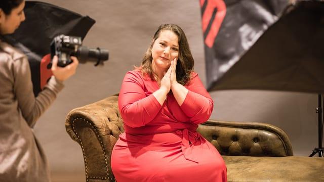 Eine füllige Frau im roten Kleid bei einem Fotoshooting.