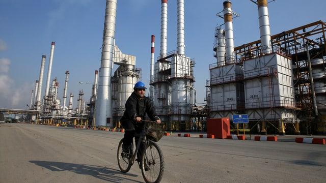 Ein Mann fährt auf einem Velo vor einer Ölraffinerie vorbei.