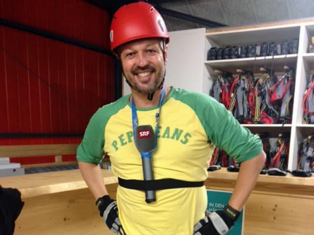 Ein Mann mit Helm trägt einen Bauchgurt, indem ein SRF-Mikrofon steckt.