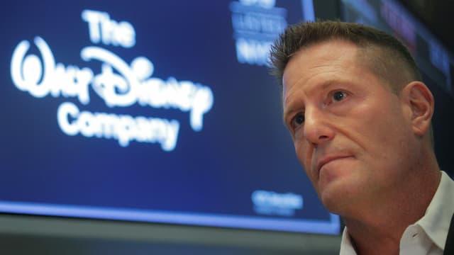 Mann vor Disney-Logo.