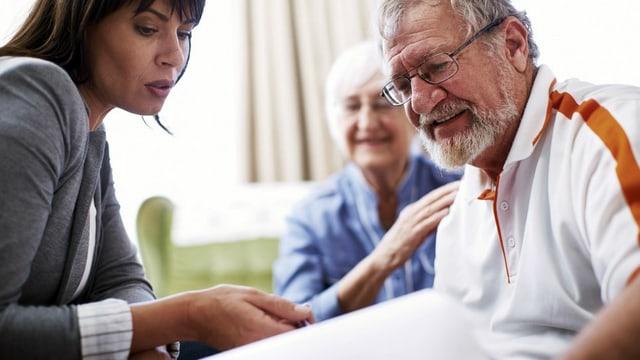 Eine Frau berät ein älteres Ehepaar.