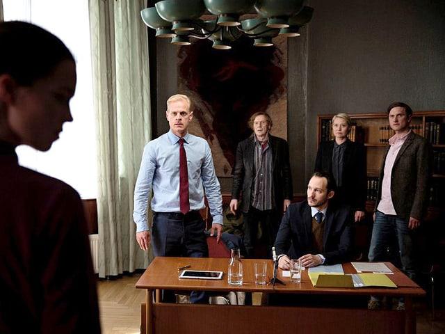 Vier Personen stehen hinter einem Schreibtisch, an welchem ein Notar sitzt.