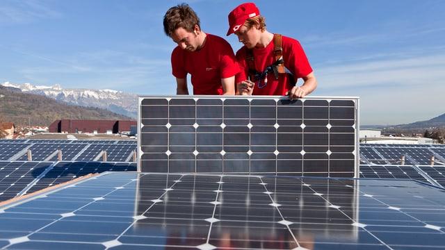 Zwei Männer montieren Solarzellen auf einem Hausdach.