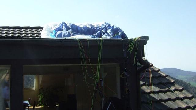 Gleitschirm des abgestürzten Piloten auf einem Hausdach.