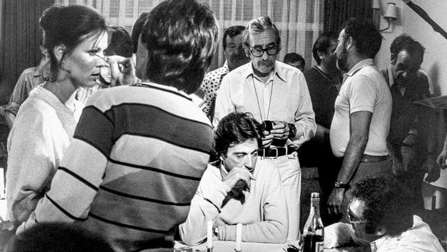 Filmset: Viele Personen in einem Raum, eine wird geschinkt, zwei sitzen an einem Tisch.