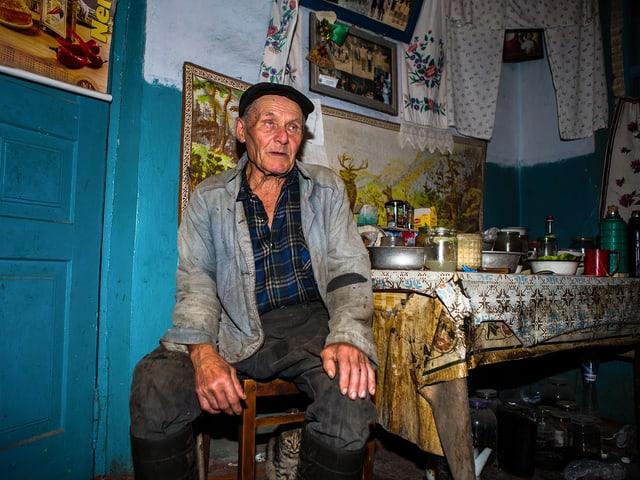 Ein älterer Mann in schmutzigen Arbeitskleidern sitzt an einem überfüllten Küchentisch.