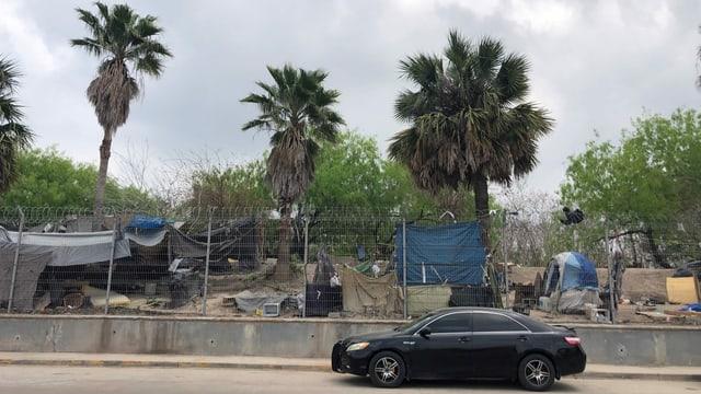 Auto steht vor Zaun hinter dem Reste des aufgelösten Asylcamps in Matamoros.