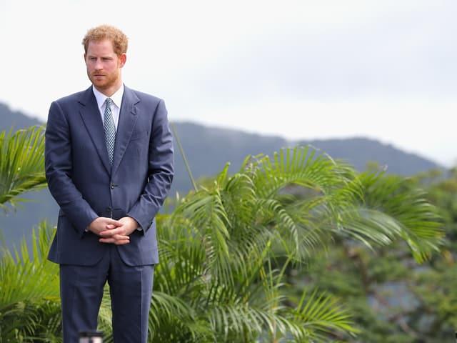 Prinz Harry vor Palmen stehend. Er schaut sehr ernst.
