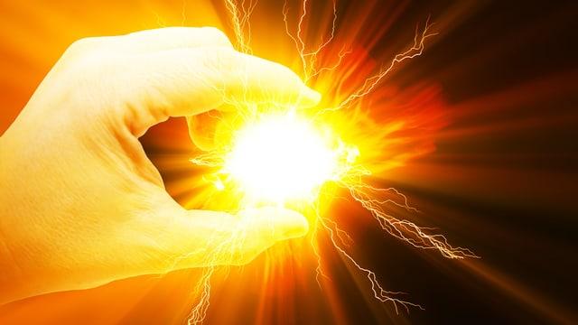 Eine Hand hält eine stark leuchtende Kugel hoch.