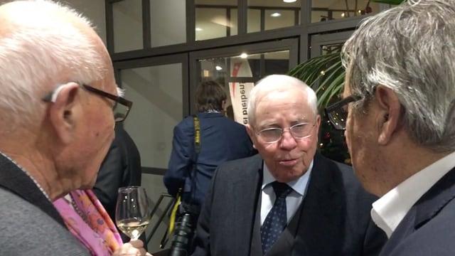 Drei Männer stehen im Kreis und sprechen miteinander.