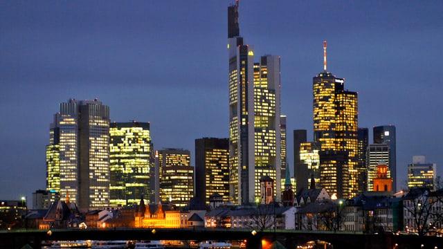 Blick auf die abendliche Skyline mit beleuchteten Wolkenkratzern.