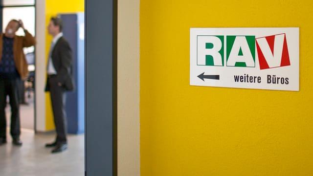 Eine gelbe Wand, darauf ein RAV-Schild.